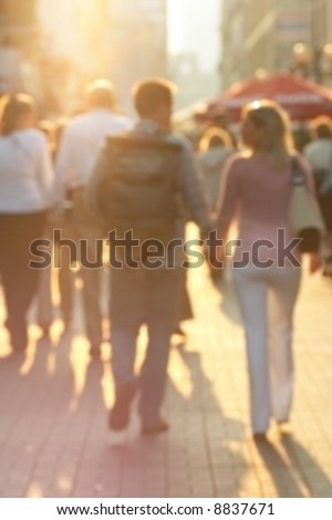 Busy European street at sunset. Purposely blurred with lens. - stock photo