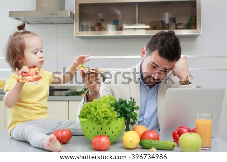 Busy father and his child have fun during lunch - stock photo