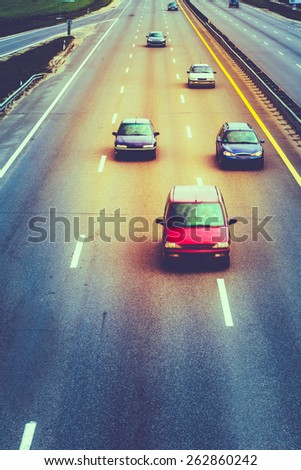 Busy Highway During Day. Heavy Traffic Moving At Speed On Motorway. Number Plates And Car Logos Removed. Toned, Instant Photo - stock photo