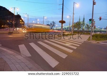busy intersection at night with cars buses and trams passing by - stock photo