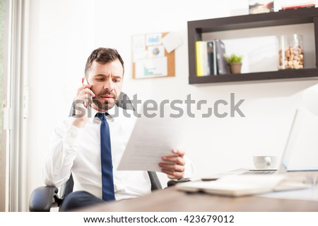 Busy lawyer taking an important phone call on his smartphone and reviewing some documents in his office - stock photo