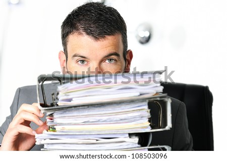busy man hiding behind a stack of files - stock photo