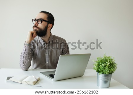 Busy man with beard in glasses thinking over laptop with smartphone on the table - stock photo