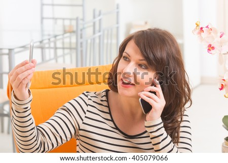 Busy mature smiling woman talking on the phone and holding second one in the other hand at home - stock photo