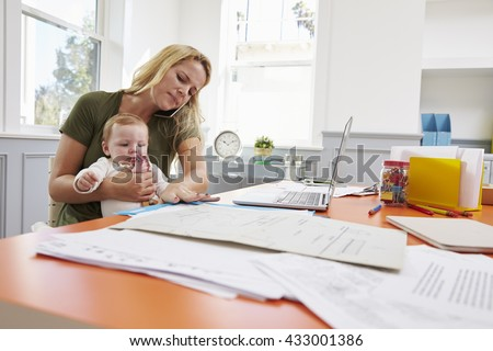 Busy Mother With Baby Running Business From Home - stock photo