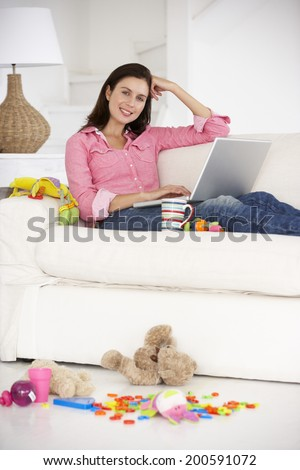 Busy mother working on laptop - stock photo