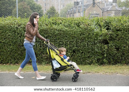 Busy Mum talking on phone while pushing her toddler sitting in a pram.