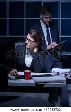 Busy office worker sitting beside desk, working at night, businessman using tablet device - stock photo