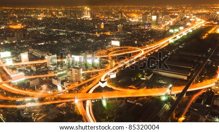Busy road intersection in the heart of downtown Bangkok, shot at night showing car headlight trails