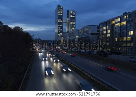 Busy road with office building in Munich, Germany, during the blue hour