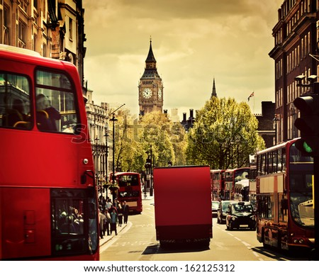 Busy street of London, England, the UK. Red buses, Big Ben in the background.  - stock photo