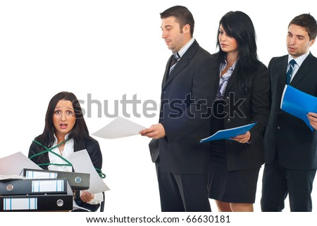 Busy stressed servant public tied in a chair at desktop working hard and other business people standing in a  row and waiting their turn to give it to her more folders for work - stock photo