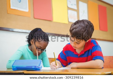 Busy students working on class work at the elementary school - stock photo