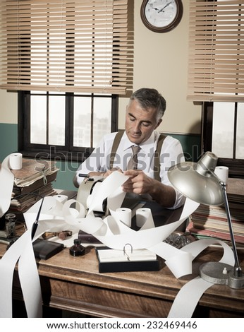 Busy vintage accountant with adding machine surrounded by cash register tape. - stock photo