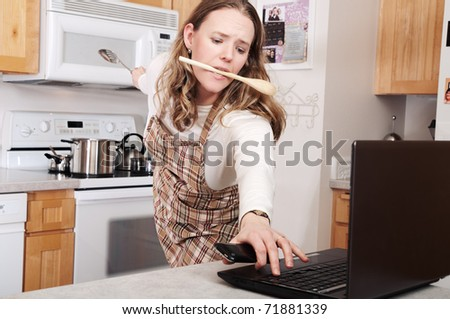 Busy woman, cooking and taking care of business on her computer and phone - stock photo