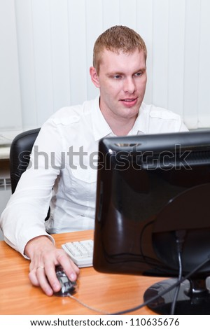 Busy young man in white shirt sitting at pc computer and working - stock photo