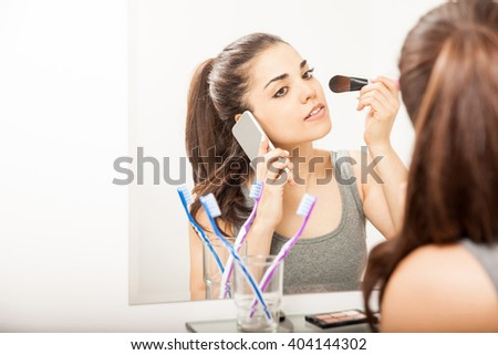 Busy young woman taking a call on her smartphone while getting ready for work and putting some makeup on - stock photo
