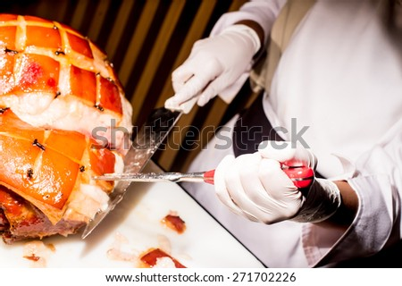 butcher's hand while fast cuts a piece of raw ham, cut ham - stock photo