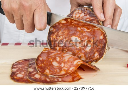Butcher slicing with a knife, a large Spanish sausage called morcon - stock photo