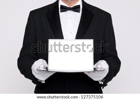 Butler holding a blank card upon a silver service tray, add your own message. - stock photo