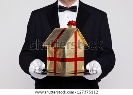 Butler holding a gift wrapped model building on a silver tray, good concept image for Moving, New Home, Relocation or House buying themes. - stock photo