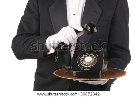 Butler Holding an Old Rotary Telephone on a tray with the receiver in his other hand isolated on white torso only - stock photo