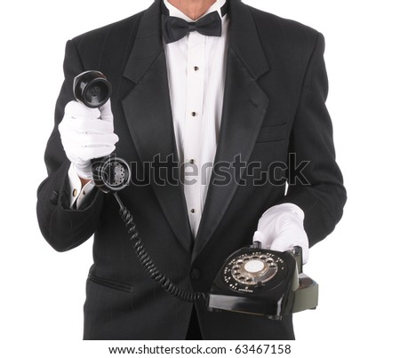 Butler Holding an Old Rotary Telephone with the receiver in one hand isolated on white torso only. - stock photo