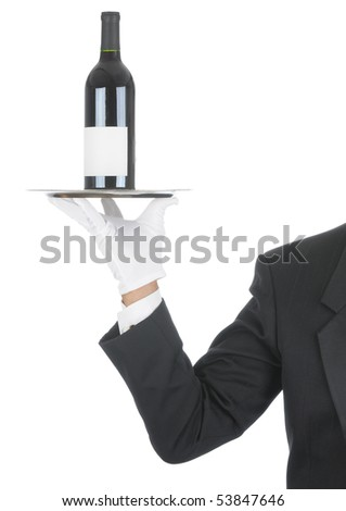 Butler wearing tuxedo and formal gloves holding a red wine bottle on a silver tray. Shoulder hand and arm only isolated on white vertical composition. - stock photo