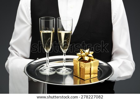 butler with gift and two champagne flutes on tray - stock photo