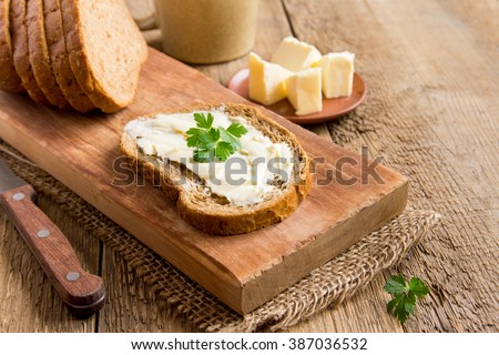 Butter and bread for breakfast, with parsley over rustic wooden background with copy space - stock photo