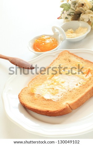 Butter and marmalade on toast for breakfast image