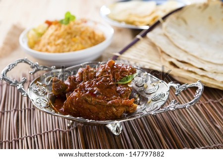Butter chicken curry with basmati rice and various indian foods at background  - stock photo