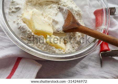 Butter, flour and sugar in a mixing bowl with a wooden spoon, pastry blender on the side - stock photo
