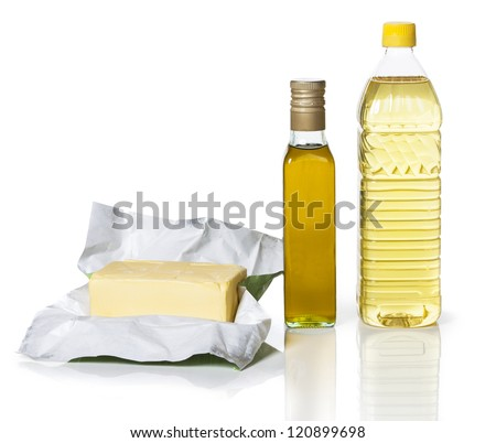Butter in paper and two bottles of different types of oil on white background