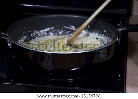 Butter melting in black saute pan being stirred with a wooden spoon - stock photo