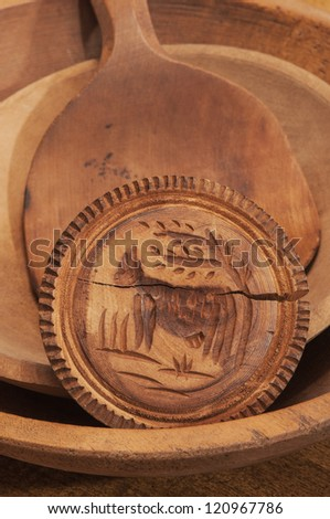 Butter mold/stamp resting on wooden spatula inside two nested wooden bowls.
