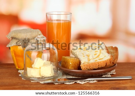 Butter on glass saucer with glass cover and fresh bread,honey, on bright background - stock photo