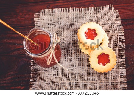 Butter sugar cookies shaped like flowers with apricot jam on rustic burlap. Shallow depth of field