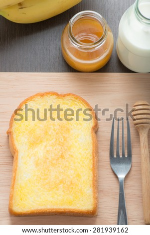 Butter toast, honey and milk on wood - stock photo