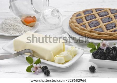 Butter with blackberries, egg, flour and blackberry tart on white wooden table. - stock photo