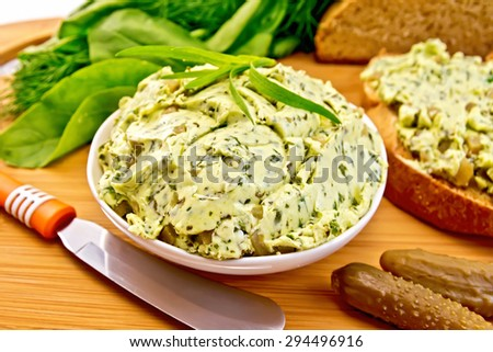 Butter with spinach, greens and pickled cucumbers in a bowl, knife, bread on a wooden boards background - stock photo