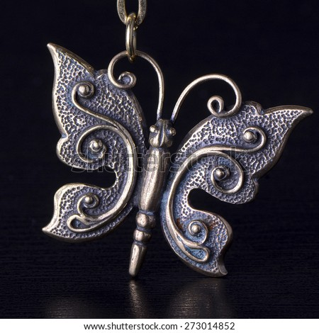 Butterfly as trinket or pendant, close up isolated on black background