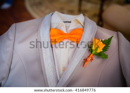 butterfly of orange color on a neck at the man. Man wears purple, purple bow-tie. The bridegroom going to the wedding. Wedding morning. The man straightens his tie. - stock photo