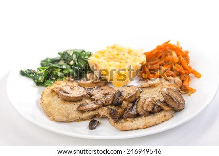 Butterfly Pork Loin smothered in sauteed mushrooms and served with wilted garlic-spinach, twice baked potato and glazed carrots. Selective focus with copy space. - stock photo
