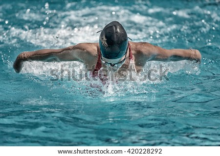 Butterfly stroke swimming. High speed action, toned image - stock photo