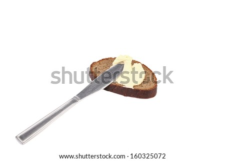 Buttering knife on brown bread. Isolated on a white background - stock photo