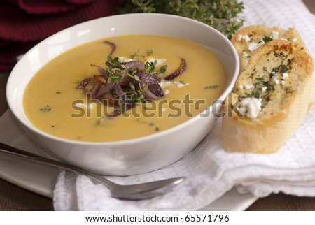 Butternut squash soup topped with goat's cheese and onion