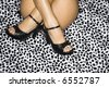 Buttocks and thighs of nude Caucasian female wearing high heels sitting with ankles crossed on leopard print. - stock photo