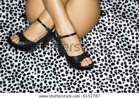 Buttocks and thighs of nude Caucasian female wearing high heels sitting with ankles crossed on leopard print.