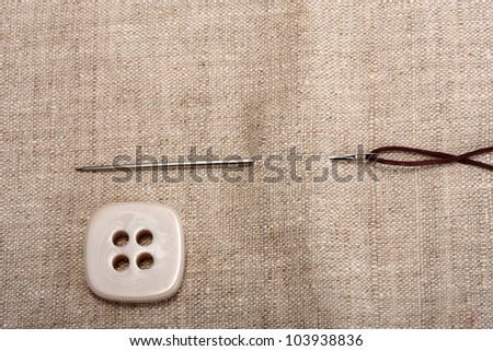 button needle and thread on background fabrics - stock photo